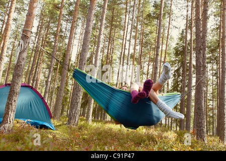 Women relaxing in hammock at campsite - Stockfoto