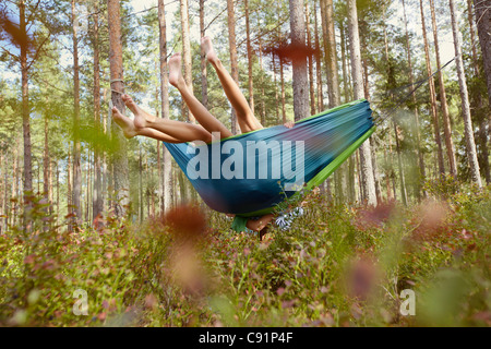 Women relaxing in hammock in forest - Stockfoto