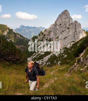 Man hiking on mountain path - Stock Photo