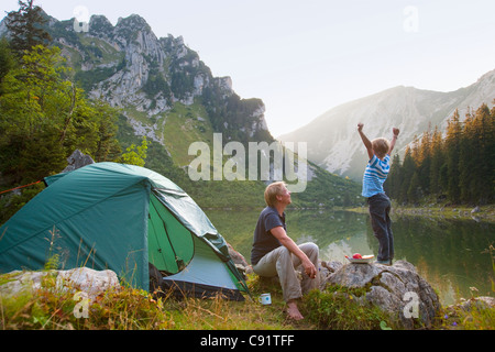 Father and son relaxing at campsite - Stockfoto