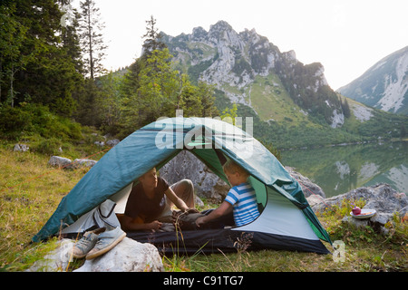 Father and son relaxing in tent - Stockfoto