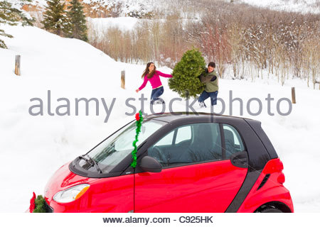 Young couple haul their cut Christmas tree to their red Smart Car in deep snow, Park City, Utah, Winter - Stock Photo