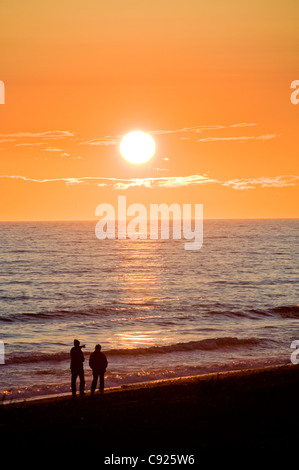 A couple walks the Homer Spit beach at sunset along Kachemak Bay, Kenai Peninsula, Southcentral Alaska, Summer - Stock Photo