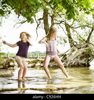 Smiling girls playing in lake - Stock Photo