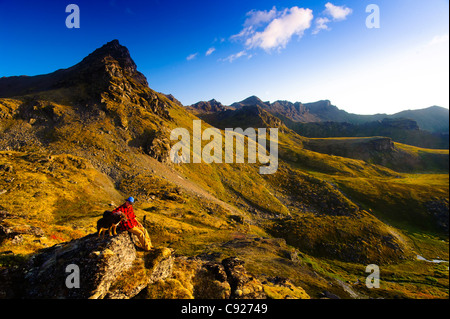 A man sitting on a rock while hiking with his dog near Hatcher Pass in the Talkeetna Mountains, Alaska - Stock Photo