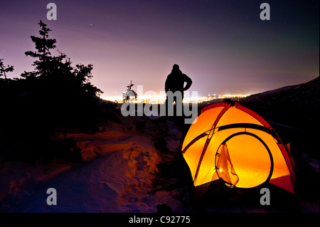 Silhouette of a man standing by a candlelit tent in Chugach State Park with the city of Anchorage in the background, - Stock Photo