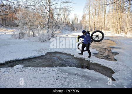 Bicyclist crosses open water of Campell Creek while carrying a snow bike in Far North Bicentennial Park near Anchorage, - Stock Photo