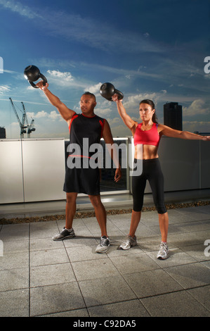 Athletes exercising together on rooftop - Stock Photo