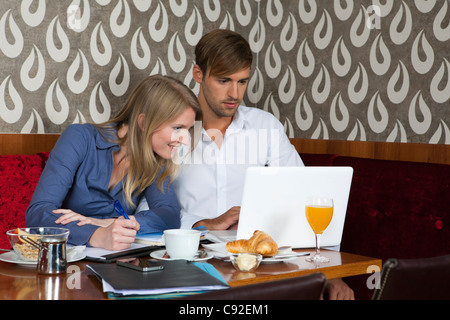 Couple studying with laptop in cafe - Stockfoto