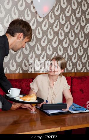 Kellner servieren Frau in café - Stockfoto