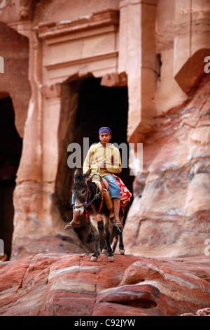 Portrait of a young beduin man riding a donkey, Petra, Jordan. - Stock Photo