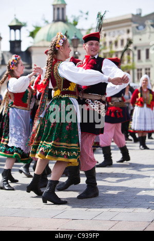 Poland, Cracow. Polish girls and boys in traditional dress dancing in Market Square. - Stock Photo