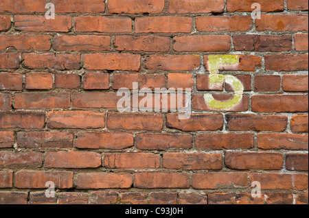 The number 5 painted on a brick wall in the Pearl District of Portland, Oregon. - Stock Photo