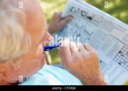 Senior man doing crossword outdoors - Stockfoto