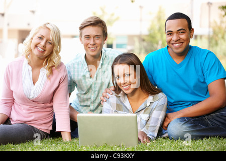 Young people using laptop outdoors - Stock Photo