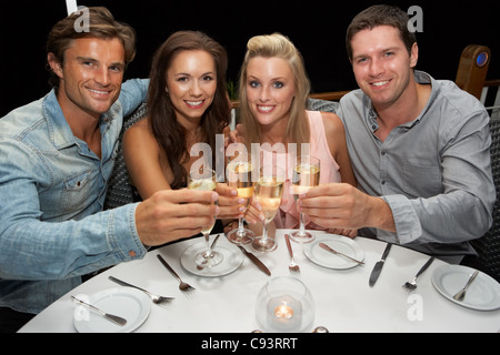Two young couples in restaurant - Stock Photo
