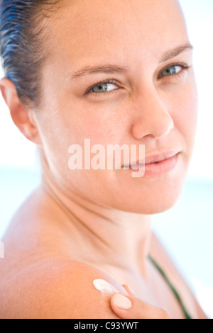 Young Woman Applying Body Lotion on Shoulder - Stock Photo