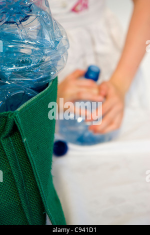 Girl's Hand Crushing Plastic Water Bottles - Stock Photo