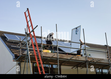 UK, Britain. Workmen fitting new solar panels to a house roof for the Feed-in Tariff scheme - Stock Photo