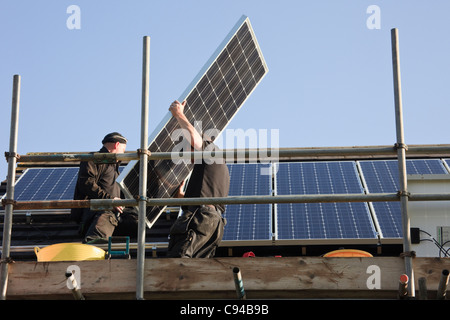 UK, Britain, Europe. Workmen fitting new solar panels to a house roof for the Feed-in Tariff scheme - Stock Photo