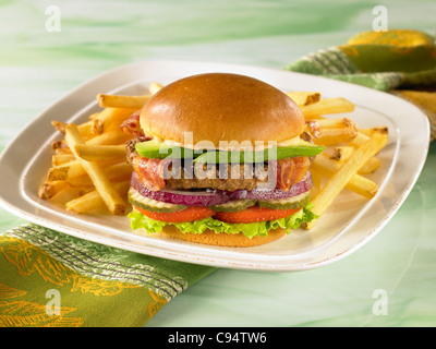 An avocado bacon burger on a bun with lettuce, tomato, pickle and onion served with french fries - Stock Photo