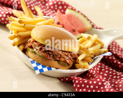 BBQ pulled pork sandwich served with french fries - Stock Photo