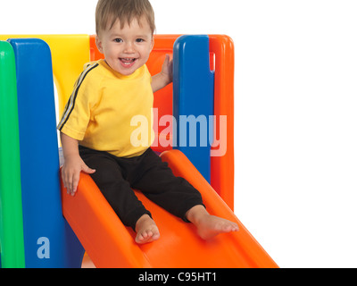 Happy one and a half year old child on a slide. Isolated on white background. - Stock Photo