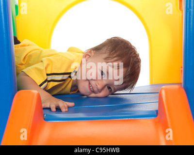 Happy one and a half year old child climbing on a slide. Isolated on white background. - Stock Photo