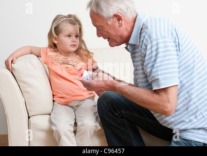 First aid for poisoning. Man asking a young girl if she has swallowed some pills. - Stock Photo