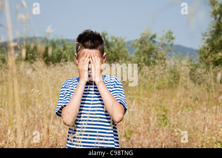 Boy playing hide and seek in field - Stock Photo