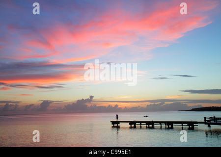 Curaçao Netherlands Antilles Dutch Piscadera Bay Caribbean Sea pier man standing rowboat coastline sunset twilight - Stockfoto