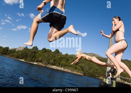 A group jumping off a pier into a lake. Lake Rosebery, Tullah, Tasmania, Australia - Stockfoto