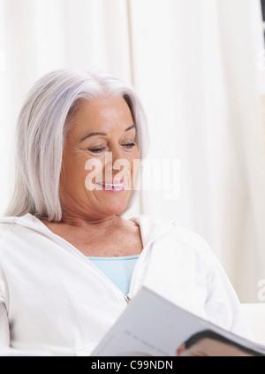Germany, Hamburg, Senior woman reading magazine, smiling - Stock Photo