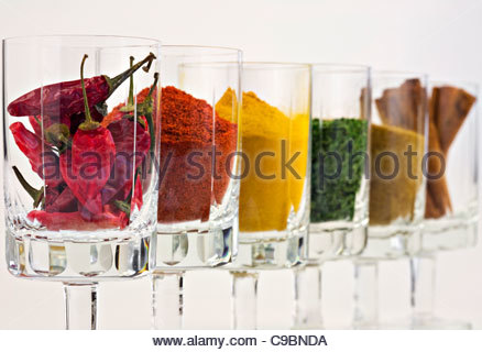 Selection of spices in glasses against white background - Stockfoto