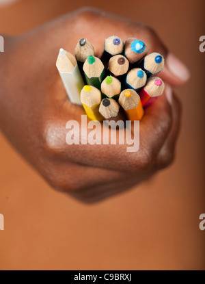 Childs hand gripping colored pencils, Johannesburg, Gauteng Province, South Africa - Stock Photo