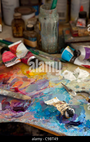 colorful artists Paint oil palette with brushes,knife,spatula,tube oils and jars. - Stock Photo