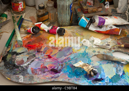 colorful artists Paint oil palette with brushes, knife, spatula, tube oils and jars. - Stock Photo