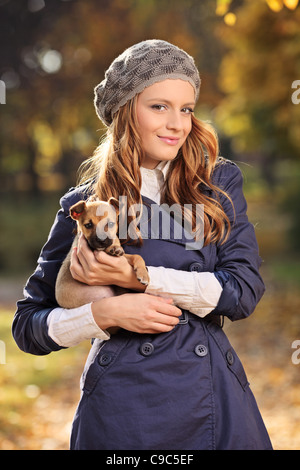 Beautiful young woman smiling and holding a puppy - Stock Photo