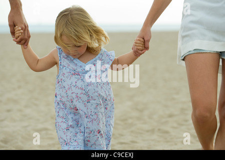 Little girl walking hand in hand with parents at the beach, cropped - Stock Photo
