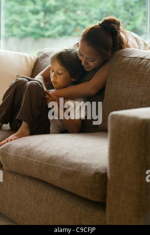 Mother and son looking at digital tablet together - Stock Photo