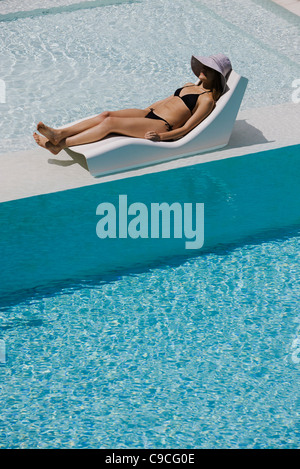 Young woman wearing sun hat reclining on poolside deckchair - Stockfoto