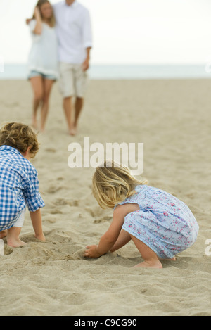Children playing in sand at the beach - Stock Photo