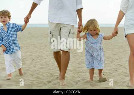Family walking hand in hand at the beach, cropped - Stock Photo
