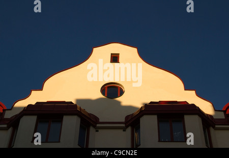 Roof top curved arched facade of building against blue sky at sunset in Stockholm Sweden - Stock Photo