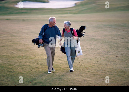 Senior couple walking on a golf course carrying golf bags - Stockfoto