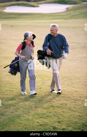 Senior couple walking on a golf course holding golf bags - Stockfoto
