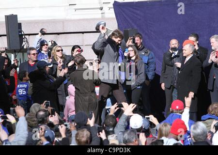 Eli Manning, hoisting the Lombardi Trophy at a public appearance for New York City Hosts Celebration for Super Bowl - Stock Photo