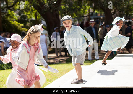 Children dressed in their Easter finest play tag before the start of the annual Hat Ladies Easter promenade on April - Stock Photo
