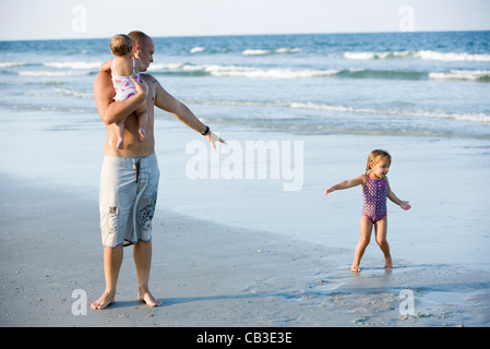Father with young daughters at the beach - Stock Photo