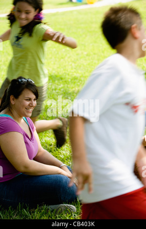 A boy and a girl running around their teacher sitting on the grass at a park - Stock Photo